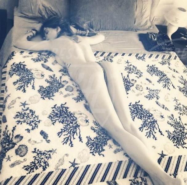 Asia Argento nuda sul letto: tattoo e seno in vista!