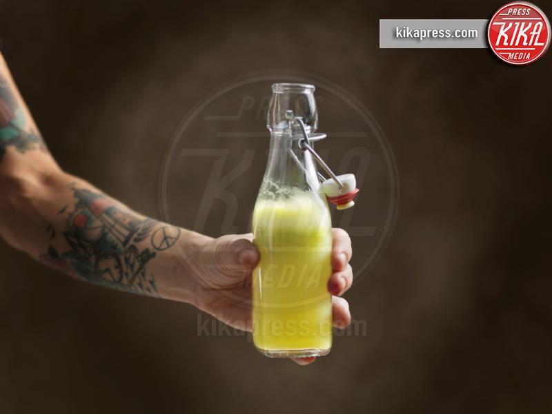 Tattooed womans arm holding raw juice in glass bottle - 11-05-2017 - Integratori di proteine:consigli su come orientarsi