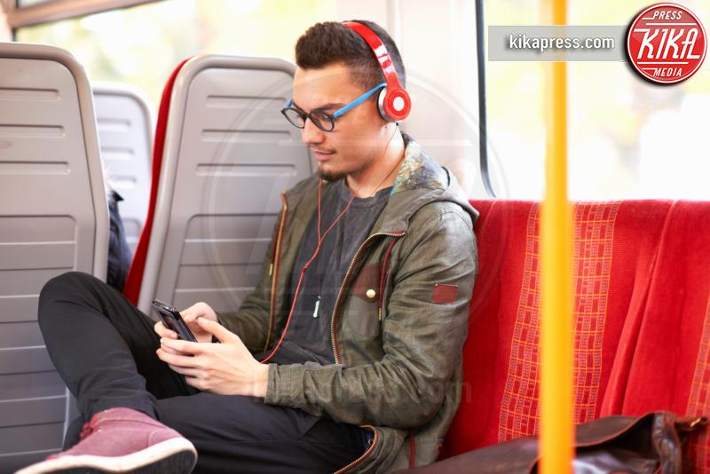 Young man sitting on train, wearing headphones, using smartphone - 11-05-2017 - Differenze di genere: il settore gioco subisce ancora influenze?