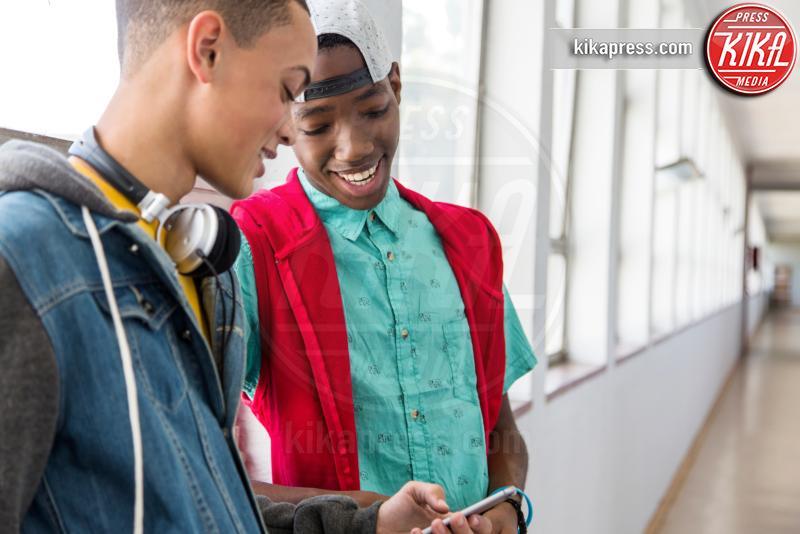 Students standing in hallway, using smartphone - 11-05-2017 - Differenze di genere: il settore gioco subisce ancora influenze?