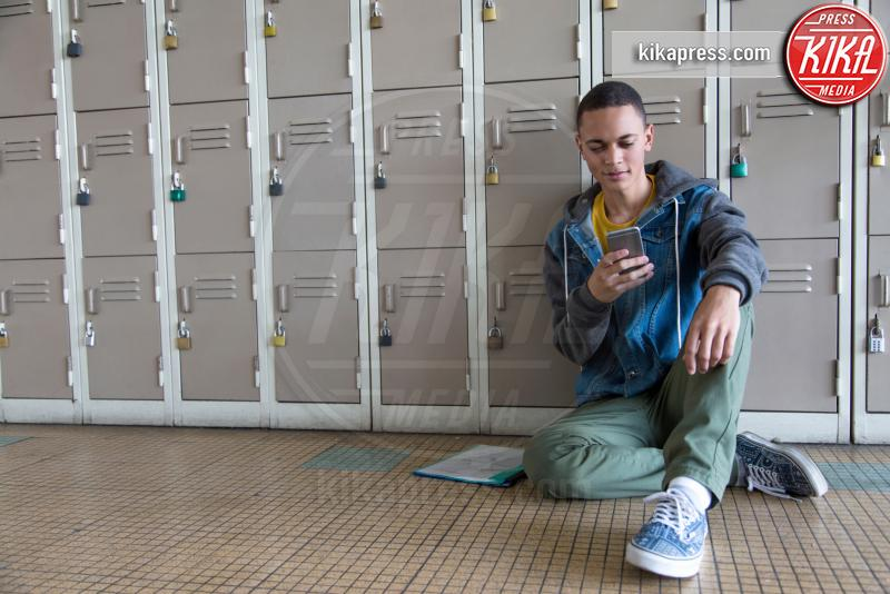 Student leaning against lockers, using smartphone - 12-05-2017 - Differenze di genere: il settore gioco subisce ancora influenze?