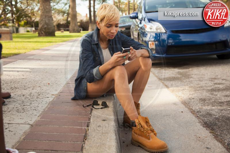 Young woman sitting on kerb, using smartphone - 12-05-2017 - Differenze di genere: il settore gioco subisce ancora influenze?