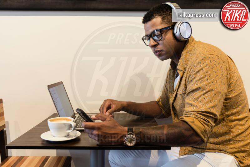 Young man in coffee shop, wearing headphones, using laptop, smartphone - 15-05-2017 - Fax sul cellulare? È possibile con eFax