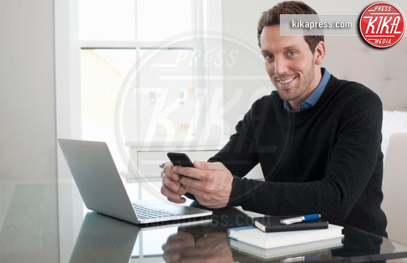 Mid adult man sitting at table, using laptop, smartphone - 15-05-2017 - Fax sul cellulare? È possibile con eFax