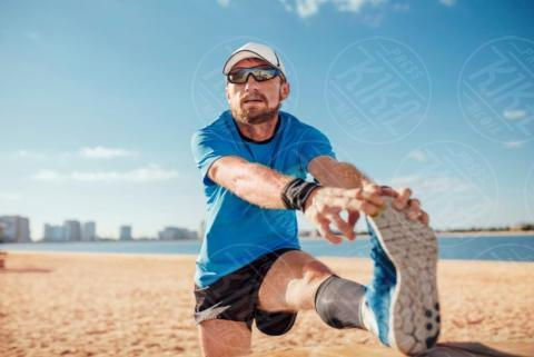 Mid adult man on beach leg raised touching toes stretching foot, UNITED ARAB EMIRATES, Dubai - 16-05-2017 - Benessere: dalle bilance intelligenti ai braccialetti fitness